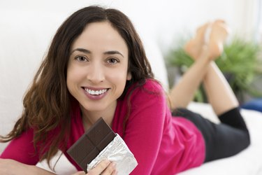 Woman enjoying chocolate while relaxing at home