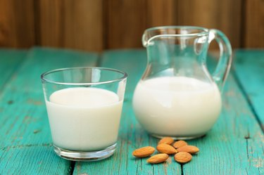 Homemade fresh almond milk in glass jar and glass bowl