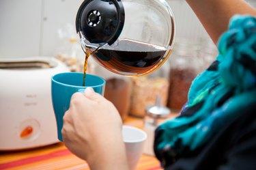 woman pouring coffee pot  into coffe mug