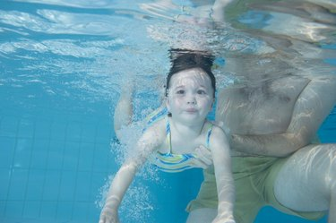 Girl (3-5) swimming underwater supported by father, close-up