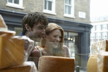 Young couple looking in store window, view from inside store