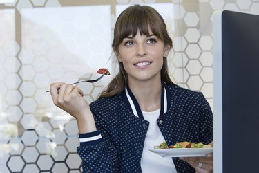 Happy businesswoman having lunch in an office