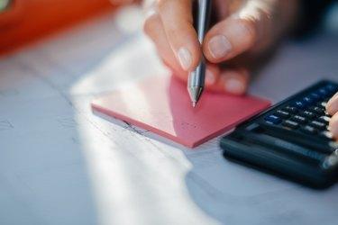 Woman hand, calculator and ball pen