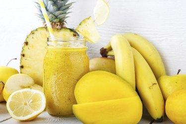 Fresh organic yellow smoothie with banana, apple, mango, pineapple