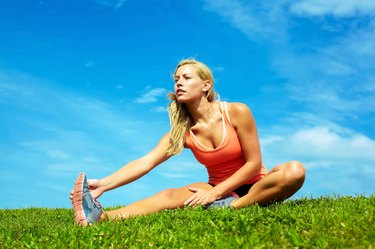 Young Female Athlete Stretching At Park