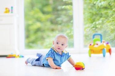 Fanny baby with toy in sunny nursery next big window