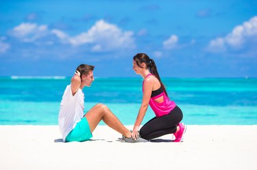 Young happy fitness couple doing sit ups on white beach