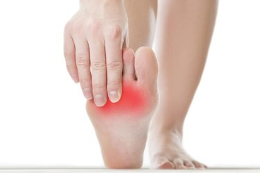 Pain in the foot. Massage of female feet. Pedicures. Isolated on white background.