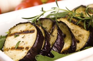 Grilled eggplant slices on a plate with fresh rosemary