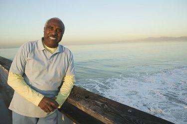 Portrait of a mature man leaning against railing on a bridge