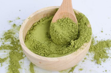 green powder heap isolated on white background
