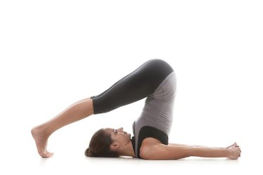 Sporty yoga girl on white background in pose halasana (Plow pose)