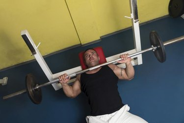 Bodybuilder In Gym Exercising On The Bench Press