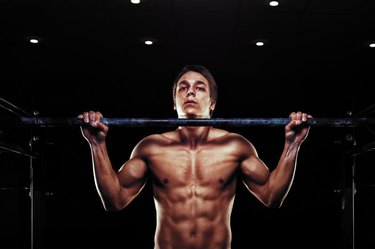 Young muscular man doing pull ups exercise on horizontal bar. Sports, fitness concept.