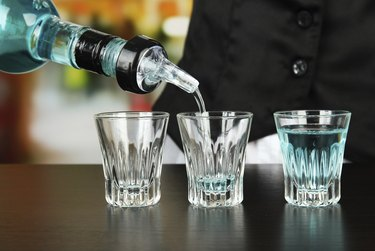 Barmen hand with bottle  pouring beverage into glasses