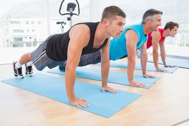 Group of men working on exercise mat