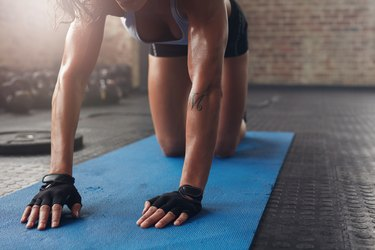 Female on exercise mat doing stretching workout. Focus on hand of a woman on fitness mat.