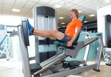 Gym seated leg press machine blond man workout