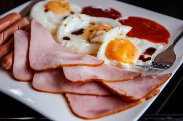 Breakfast consists of Fried egg, bacon, sausage