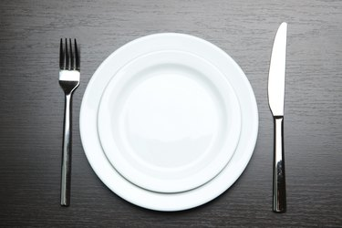 Knife,  plate and fork, on wooden background