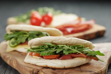 rustic sandwiches with ham arugula and tomatoes in pita bread