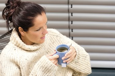 Woman drinking cup tea knitted sweater relaxing
