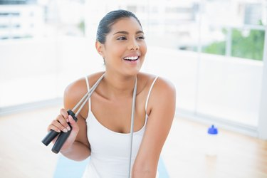 Cheerful toned brunette sitting on floor with skipping rope