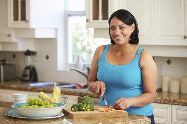 Overweight Woman Preparing Vegetables In Kitchen