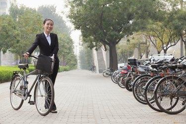 Young businesswoman holding a bicycle, sidewalk, Beijing