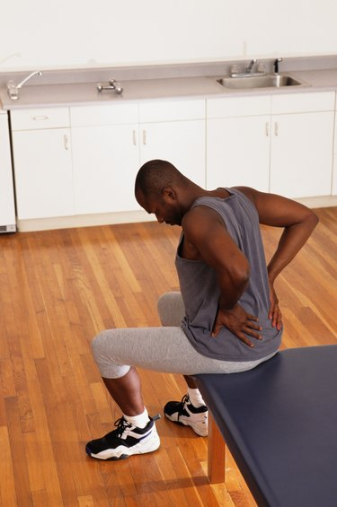 Man sitting on bed in physical therapy centre with back pain, elevated view
