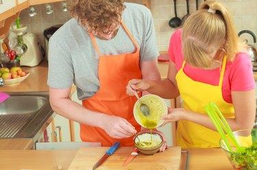 Couple preparing fresh salad dressing