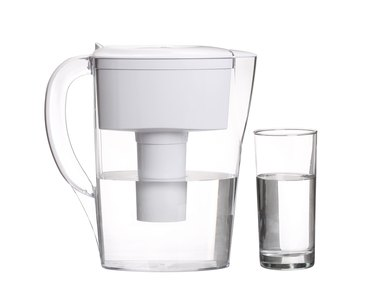 water filter jug with glass of clean water isolated