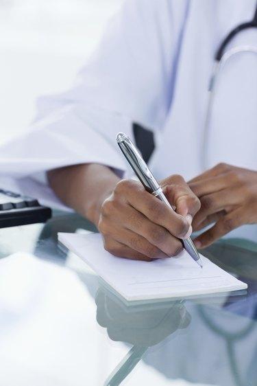 Portrait of a feminine hand writing on the prescription pad