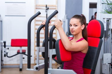 Young, adorable, cute, sexy trainer girl doing her butterfly chest workout exercise on the Pec Deck expressing power and strength in red sportswear