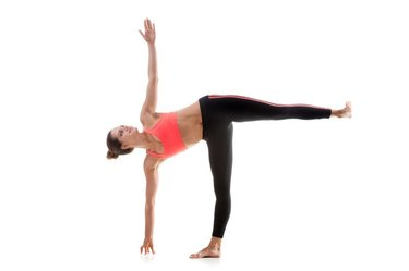 Sporty yoga girl on white background in ardha chandrasana (Half Moon Pose)
