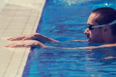 Well built sportsman swimming.