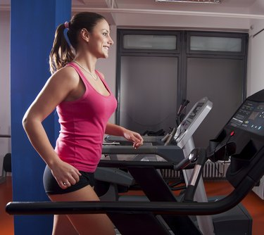 Beautiful smiling girl running on treadmill