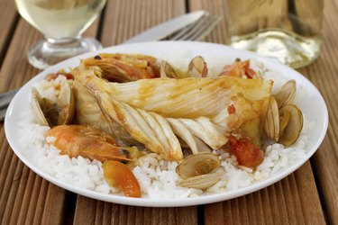fish with seafood and rice on the plate
