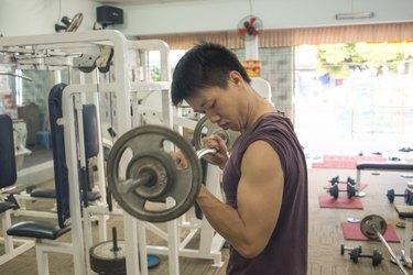 Handsome Bodybuilder performing barbell biceps curls