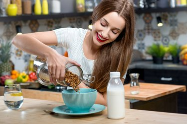 Woman with granola breakfast in the kitchen