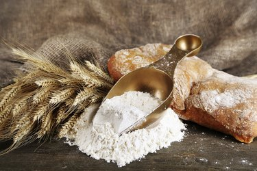 The wholemeal flour in scoop on wooden table
