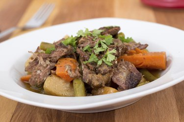 braised beef pot roast stew with vegetables on table