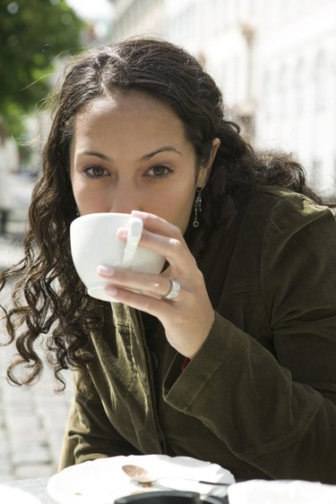 lifestyle portrait of a young adult woman as she sips from her cup at an outdoor cafe