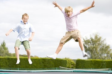Two young boys jumping on trampoline smiling