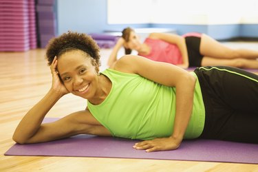 African woman laying on exercise mat in health club