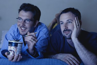 Gay couple lying on bed watching television, one eating ice cream