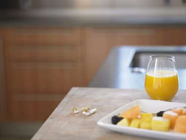 Glass of orange juice, fresh fruit and pills on kitchen counter