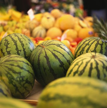 Several water melons on a fruit stall at the market