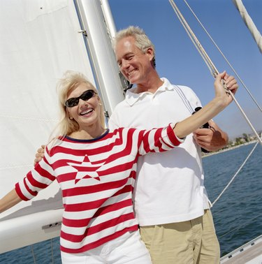 Mature couple standing on yacht, smiling