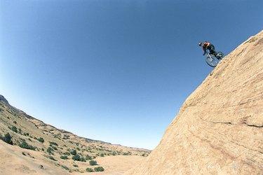 Young man riding bike down mountain, side view